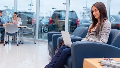 A woman using her laptop inside a car dealership.