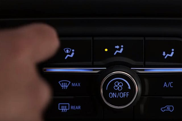 User adjusting climate control on dashboard