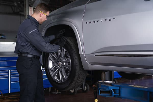 A service technician checking for a tire wear